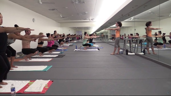 yoga instructor teaching Bikram yoga to many students