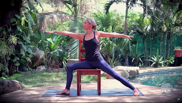 yoga teacher practicing chair yoga