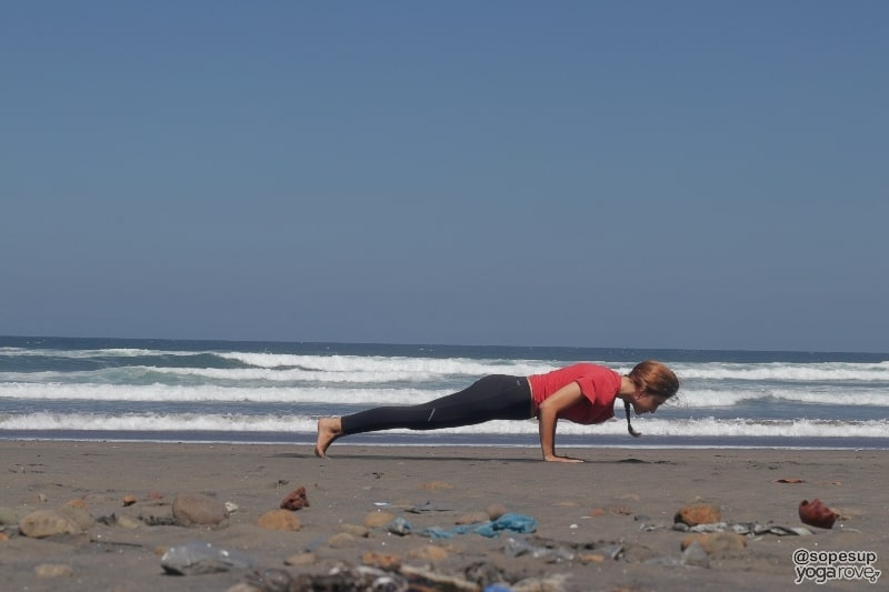 yogi practicing chaturanga on beach