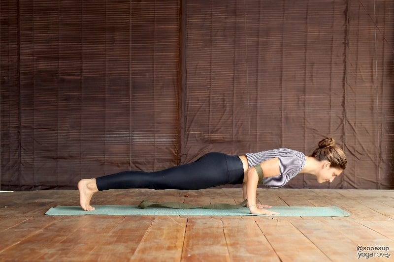 beginner yoga student practicing chaturanga with strap around arms.