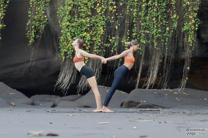 two yogis practicing balancing backbend in partner yoga.
