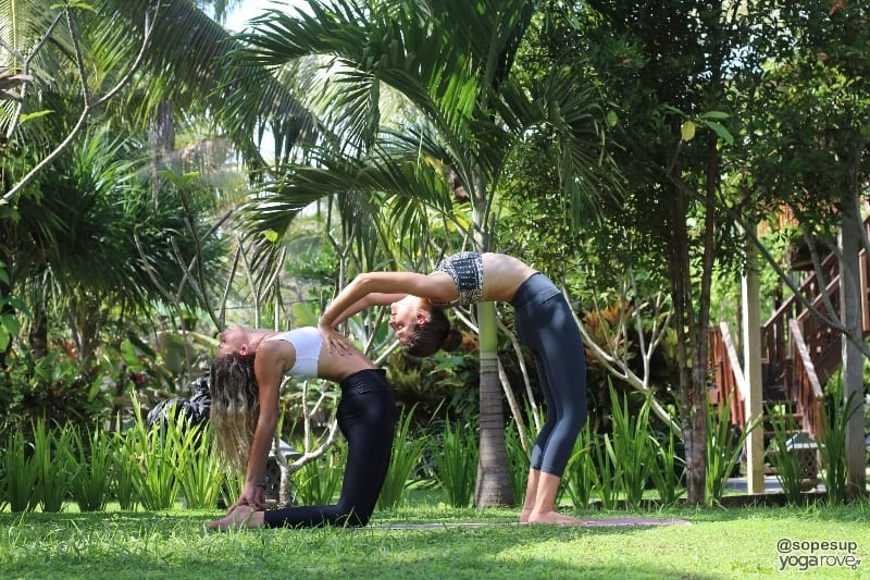 two yoga students practicing camel and supported backbend- partner yoga