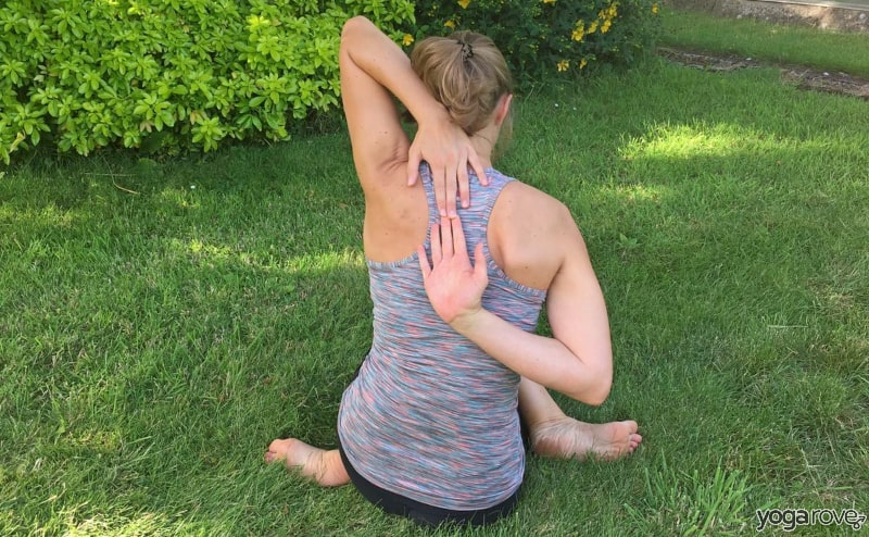 yogi practicing cow face pose for pain between shoulder blades.