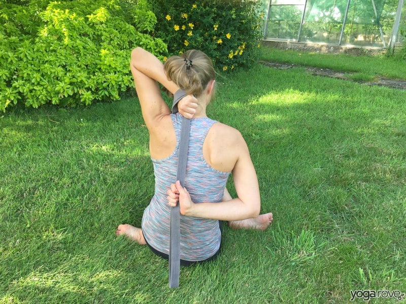 yoga students practicing cow face pose with strap for pain between shoulder blades.