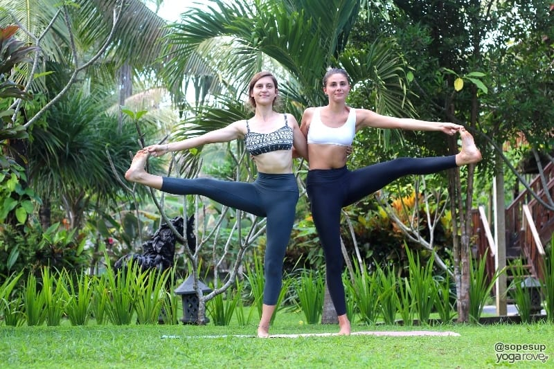 two yoga students practicing souble standing hand to big toe balancing pose- partner yoga