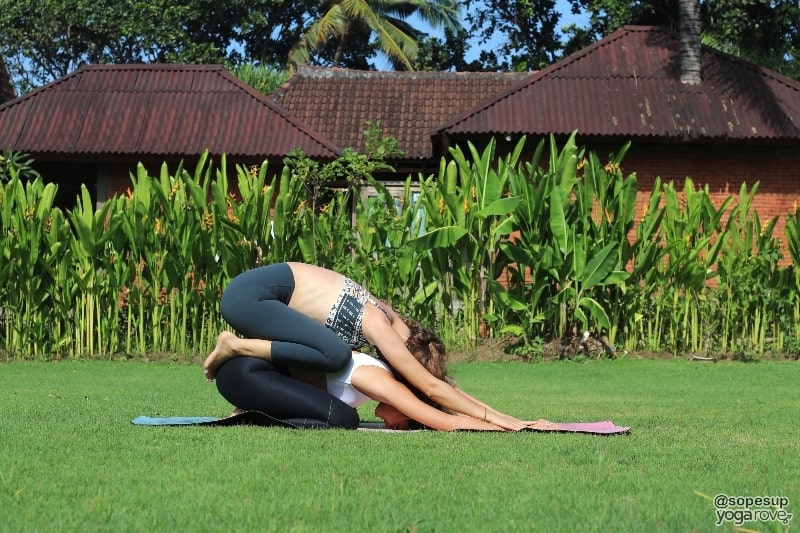 two yoga students practicing double childs pose- partner yoga