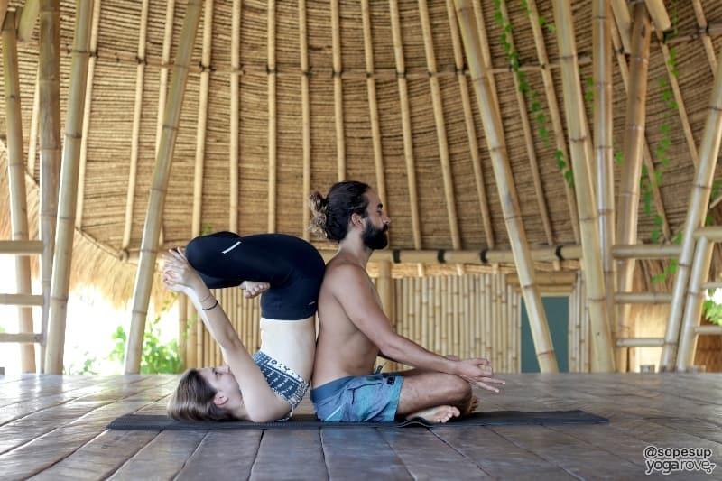 yoga students practicing double lotus pose- partner yoga