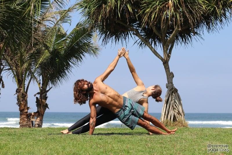 two yogis practicing side plank- partner yoga