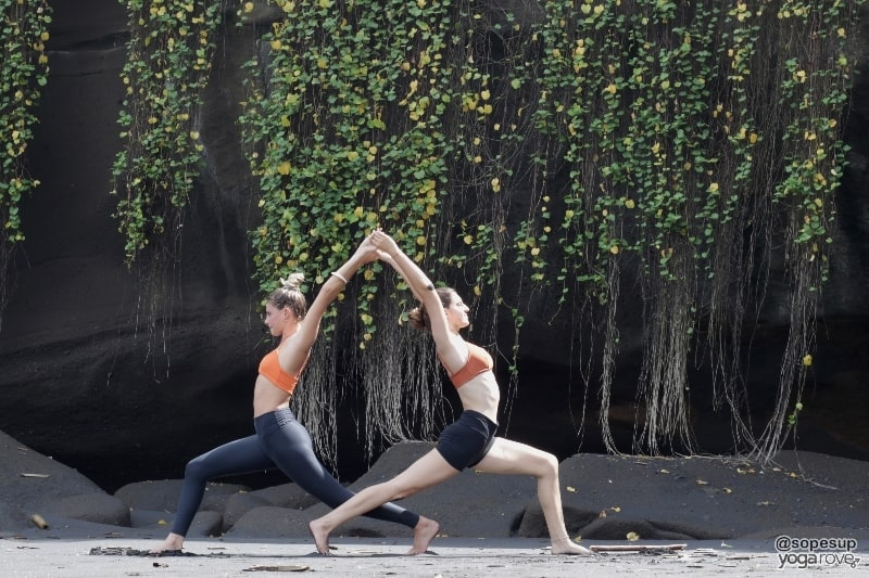 two yogis practicing high crescent lunge- partner yoga