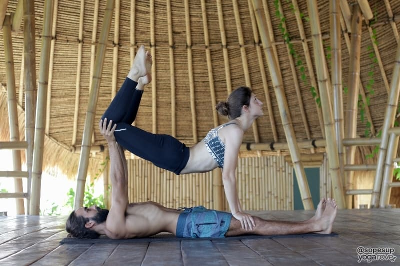 yoga students practicing lifted bow- partner yoga.