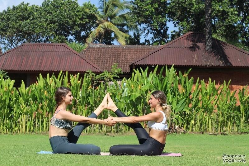 two yogis practicing one legged boat pose- partner yoga