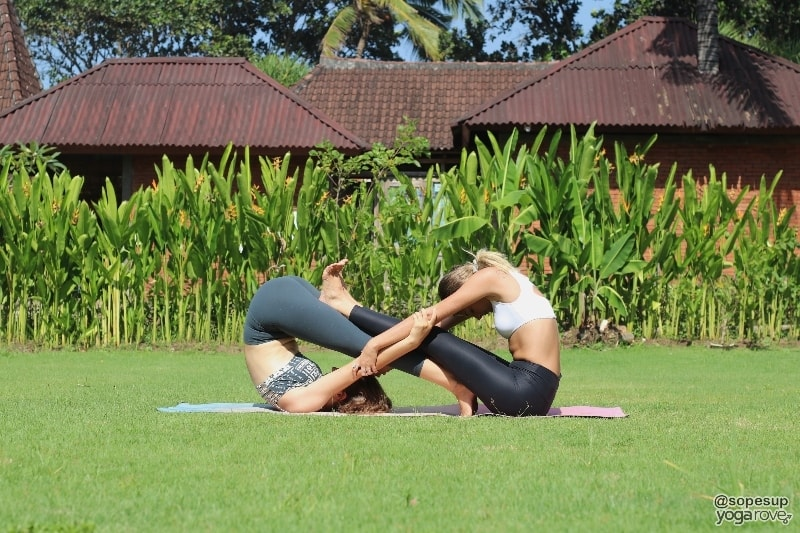 yogis practicing seated forward fold and plow- partner yoga