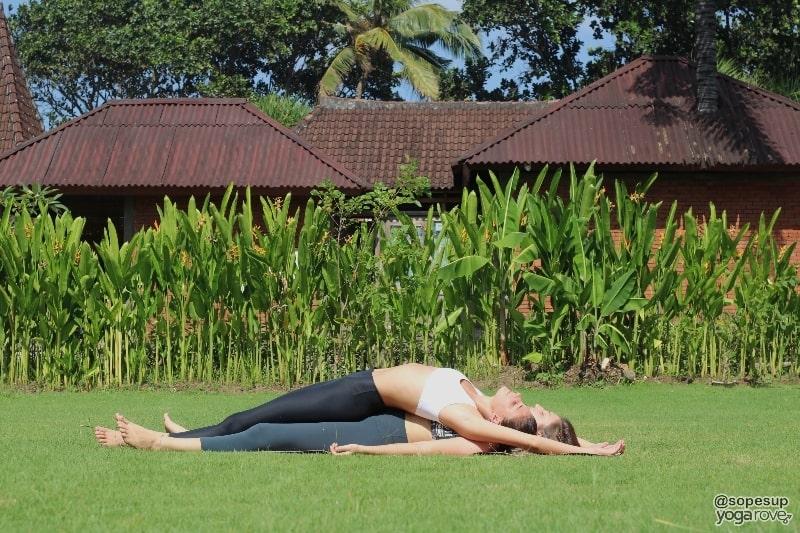 two yogis practicing savasana and supported backbend- partner yoga