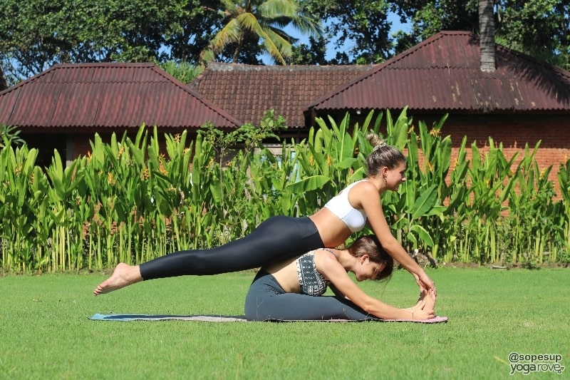 two yogis practicing seated forward fold and locust pose- partner yoga