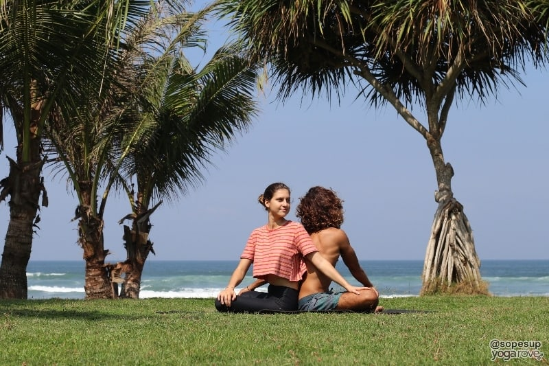 two yogis practicing seated wist- partner yoga