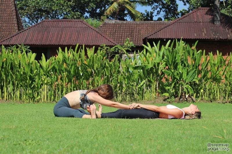 two yogis practicing seated wide legged fold- partner yoga