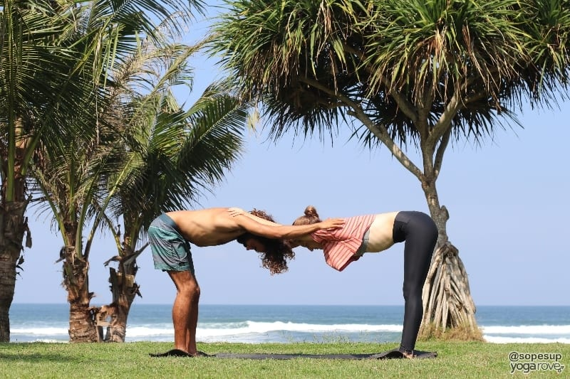 two yogis practicing standing shoulder stretch- partner yoga