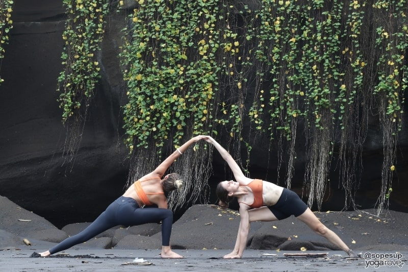 two yogis practicing extended side angle- partner yoga