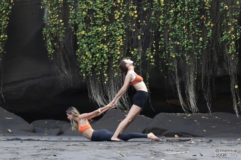 two yogis practicing standing backbend and assisted cobra pose- partner yoga