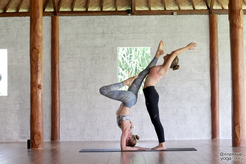 yoga students practicing supported forearm stand with standing backbend- partner yoga