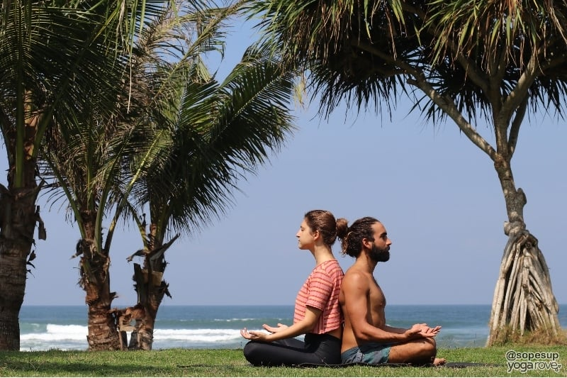 two yogis practicing partner yoga easy sukhasana pose