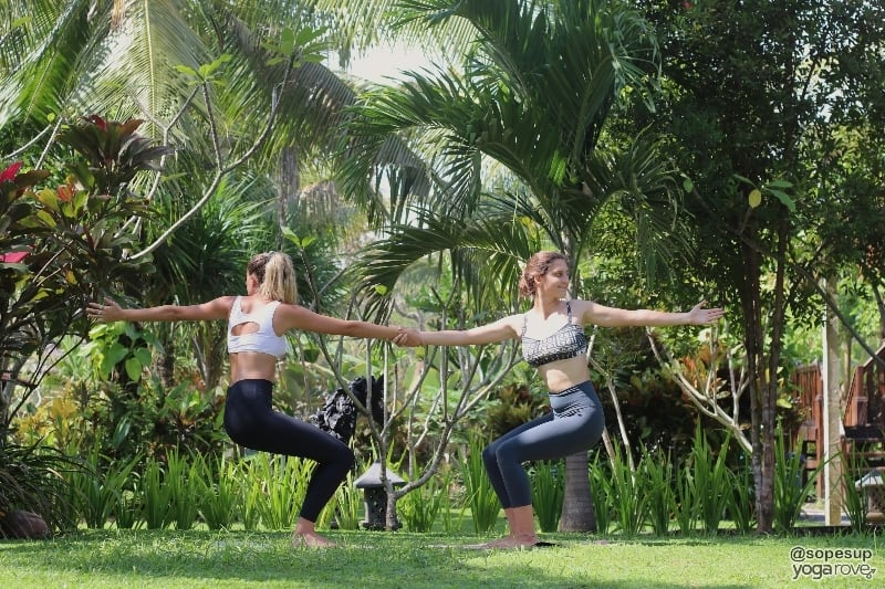two yogis practicing revolved chair pose- partner yoga