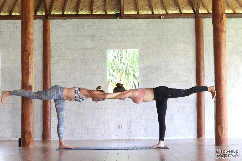 two yogis practicing warrior III- partner yoga