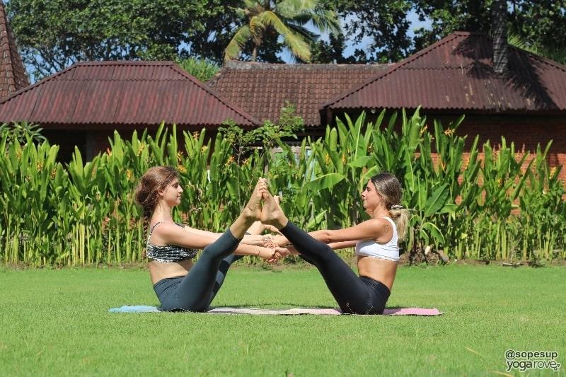 two yogis practicing wide legged boat pose- partner yoga
