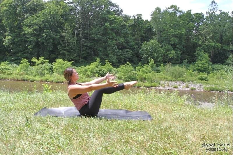 yogi practicing boat pose in sweaty yoga practice