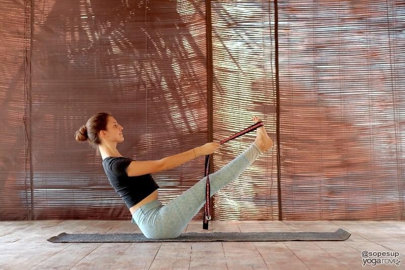 yogi practicing boat pose with yoga strap.
