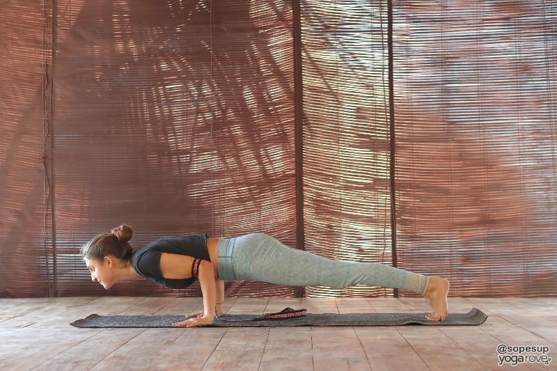 yoga student practicing chaturanga with yoga strap.
