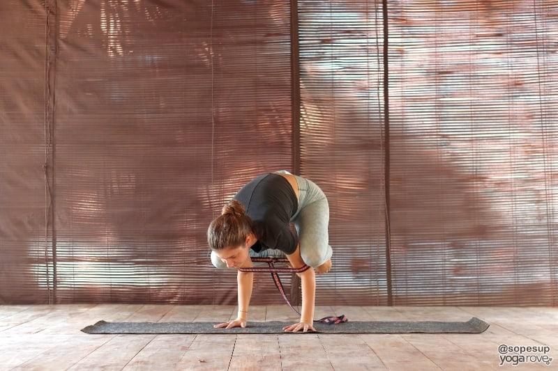 yogi practicing crow with yoga strap.