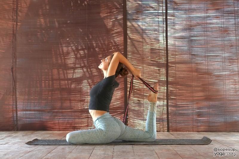 yogi practicing king pigeon pose with yoga strap.