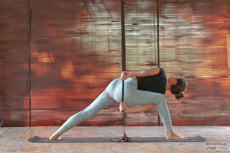 yoga student practicing side angle with bind with yoga strap.