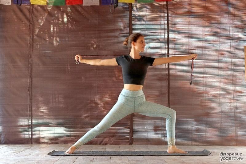 yogi practicing warrior 2 with yoga strap.