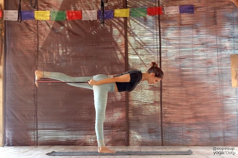 yogi practicing warrior 3 with yoga strap.