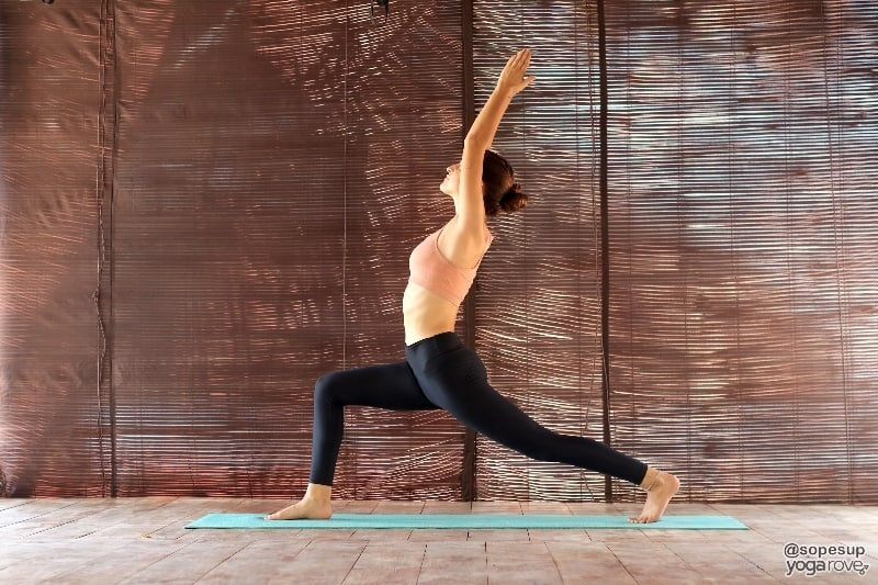 yoga student practicing high lunge to prep for boat pose