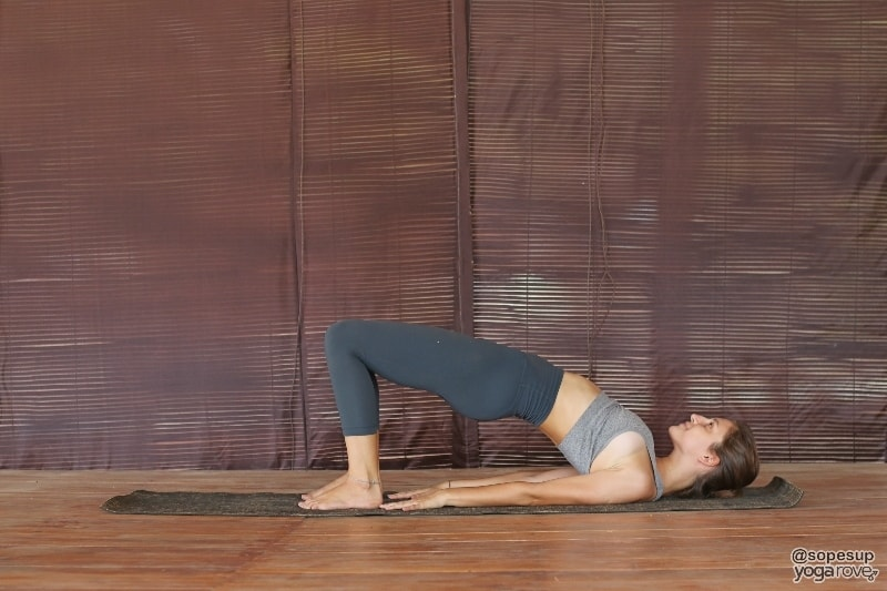 yogi practicing bridge pose on floor for weight loss.