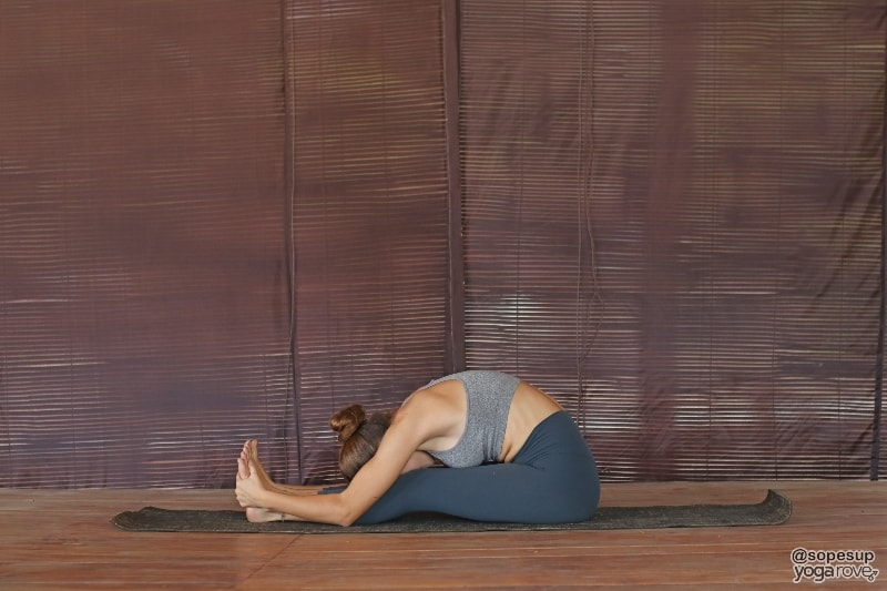 Yogi practicing seated yogi pose, seated forward fold.