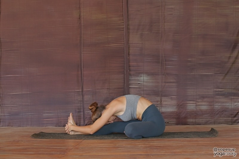beginner yogi practicing seated head to knee yoga pose.