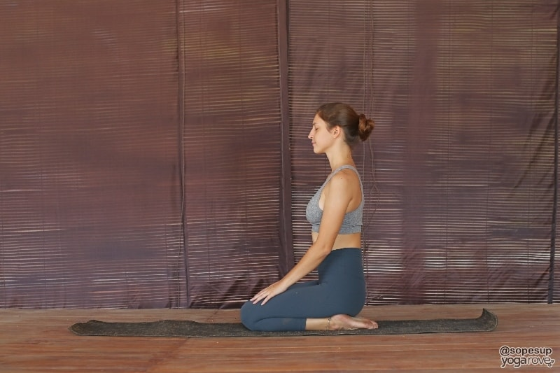 yoga student practicing hero pose in seated yoga.